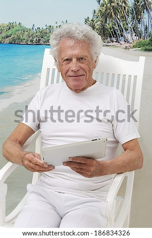 stylish  retirement senior man  seated in summer with, tropical beach background ,using tablet computer,  looking to camera  - stock photo