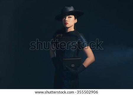 Stylish retro 1940 asian fashion woman. Holding handbag. Wearing hat. - stock photo