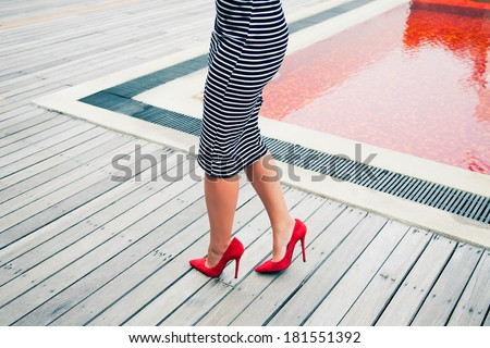 Stylish retro woman outfit with black and white striped dress red high heels classic pumps, posing near creative red pool. - stock photo