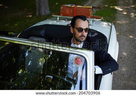 Stylish rich man in sunglasses sitting behind the wheel of cabriolet classic luxury car on the green beautiful road and thoughtfully looking away, lifestyle and successful business concept - stock photo