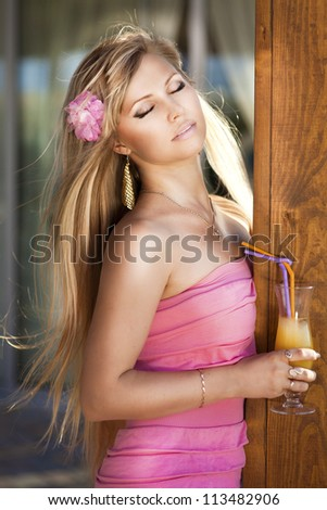 Stylish rich slim girl resting with orange drink in sexy dress in luxurious wooden interior at hotel villa. Fashion glamorous shot at vacation. beautiful blonde young woman waiting for someone - stock photo