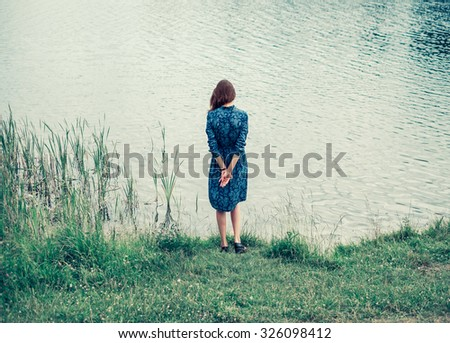 stylish romantic girl on the beach near the water in the summer in a beautiful dress - stock photo