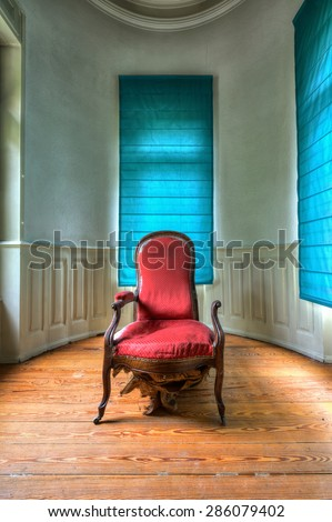Stylish room with broken old fashioned red armchair - stock photo