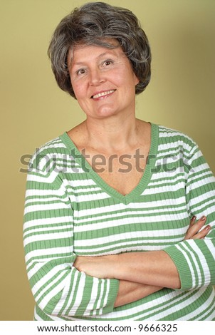 Stylish senior against a muted green background - stock photo
