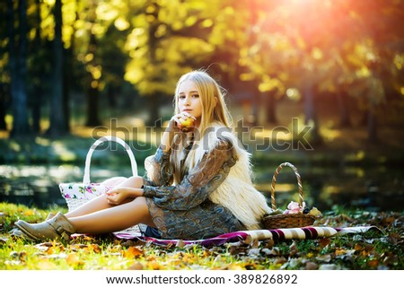 Stylish sensual thoughtful beautiful young blond girl with long hair in fashionable spring dress sitting on picnic plaid with basket of fruits in park outdoor on natural background, horizontal picture - stock photo