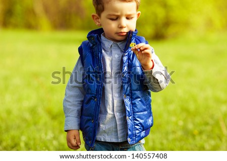 Stylish serious baby boy with ginger (red) hair in trendy striped shirt and blue jacket standing in the park and holding dandelion. Hipster style. Sunny weather. Copy-space. Outdoor shot