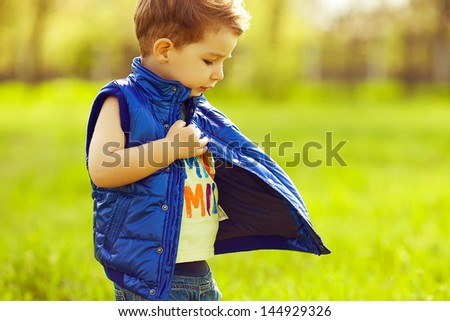 Stylish serious baby boy with ginger (red) hair wearing blue jacket, standing in the park and trying to find something in his pocket. Hipster style. Sunny weather. Copy-space. Outdoor shot - stock photo
