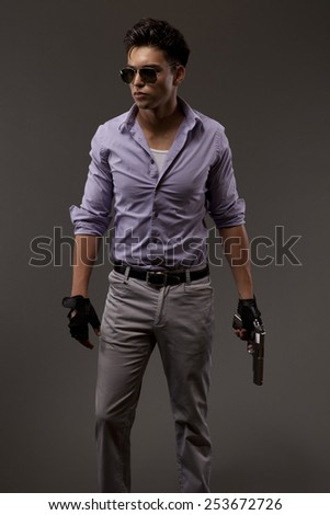 stylish shooter with handgun and glasses on grey background - stock photo
