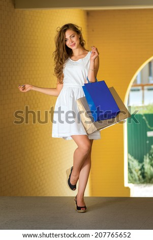 Stylish shopping. Girl holding shopping bags and take off posing for the camera outdoors - stock photo
