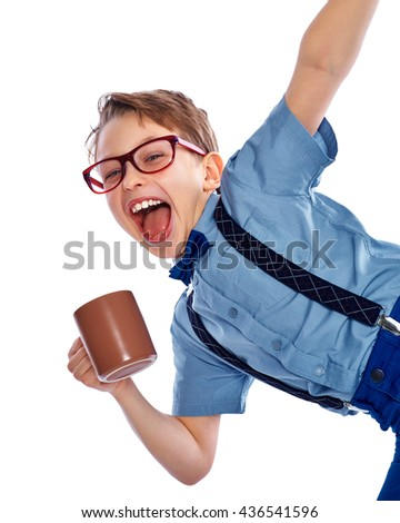 Stylish small boy in glasses holding cup of tea, coffee or juice. He is laughing and looking into the camera. Isolated on a white background. - stock photo