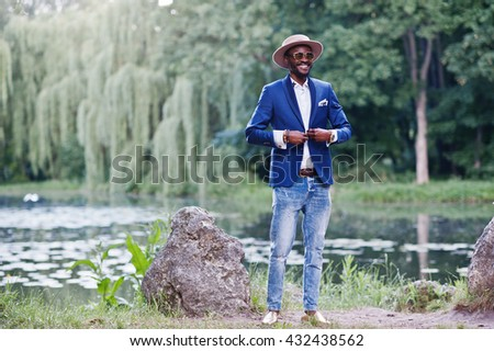 Stylish smiled african american man at blue jacket, sunglasses and hat - stock photo