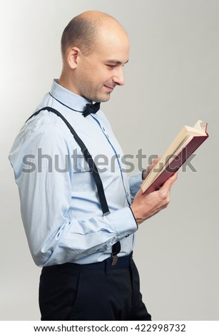 stylish smiling handsome bald man reading a book - stock photo