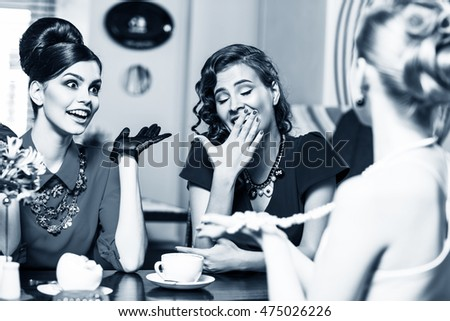 Stylish smiling women talking and drinking coffee