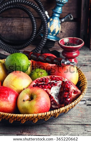 Stylish Smoking hookah and basket with apples,pomegranate and lime.Selective focus - stock photo