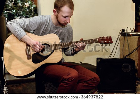 stylish solo guitarist performing on a concert on a background of his band - stock photo