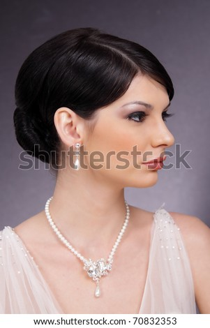 Stylish studio portrait of a beautiful young woman with pearl earrings and necklace - stock photo
