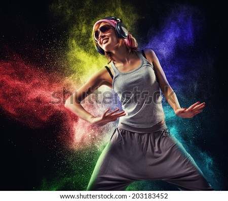 Stylish teenage girl with headphones dancing against colourful powder explosion - stock photo