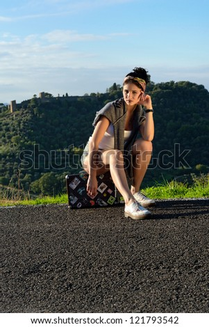 Stylish tired young girl sits on the suitcase on a rural road. Tuscan, Italy - stock photo