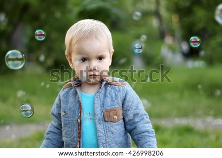 Stylish toddler boy standing among soap bubbles in the park, spring, vacation, outdoor portrait - stock photo
