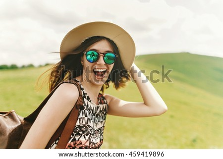 stylish traveler hipster woman in fashionable sunglasses holding hat and laughing on top of mountains, emotional happy moment, travel concept, space for text - stock photo