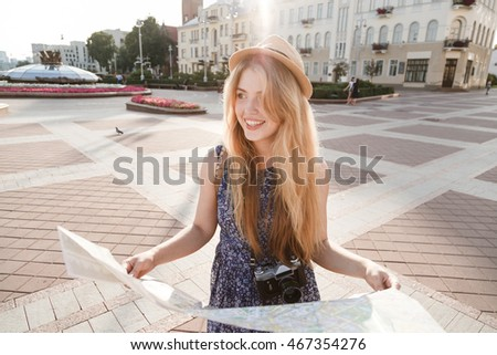 stylish traveler hipster woman portrait with camera and hat holding map on the street, travel or exploring concept