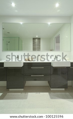 Stylish twin bathroom with two sinks and mirror. - stock photo