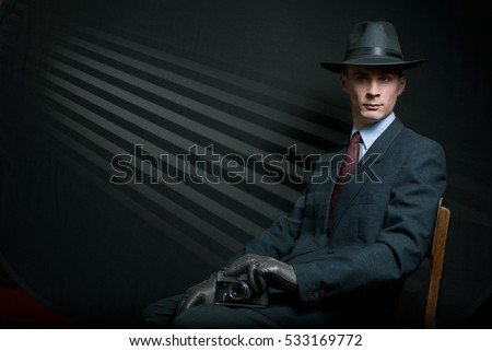 Stylish vintage detective posing on a chair in a fashionable hat , suit and gloves with his camera on his knee against a background of dark oblique parallel lines with copy space