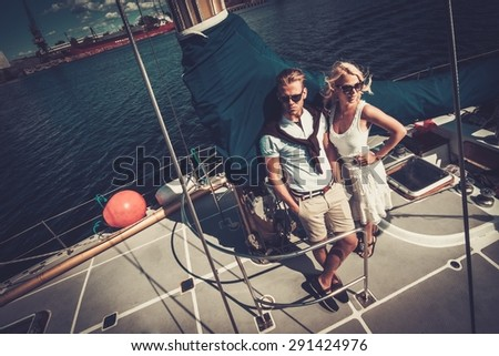 Stylish wealthy couple on a yacht  - stock photo