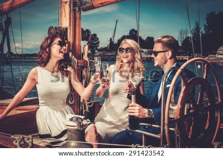 Stylish wealthy friends having fun on a luxury yacht  - stock photo
