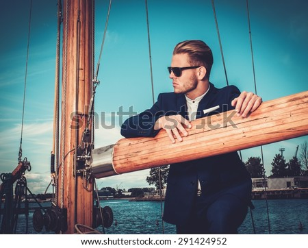 Stylish wealthy man on a luxury wooden regatta   - stock photo