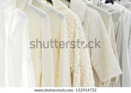 Stylish white jacket on hangers at the show - stock photo