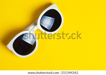 Stylish white sunglasses on yellow background - stock photo