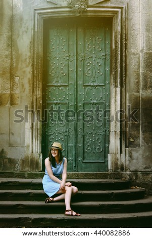 stylish woman hipster posing and sitting at old door  in european streets in sunny morning, space for text