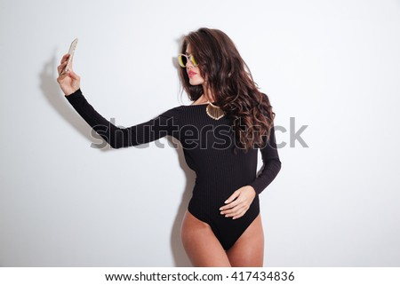 Stylish woman in bodysuit making selfie photo on smartphone isolated on a white background - stock photo