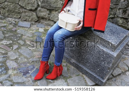 Stylish woman in bright felt red coat and blue jeans. Girl with handbag in hands sitting on the stone in the city.  Fall outfit