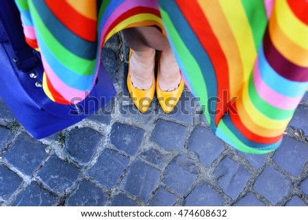 Stylish woman in rainbow skirt with blue leather handbag in hands. Woman legs in bright yellow leather heels on the city street.