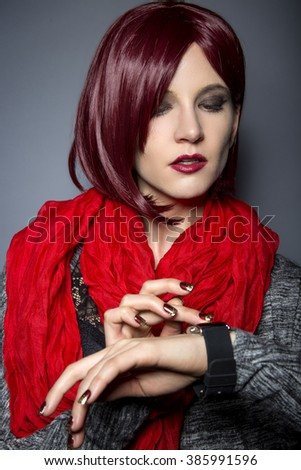 Stylish woman in red wearing an electronic smartwatch wearable tech.  The wrist watch is an electronic device with a touch screen digital display. - stock photo