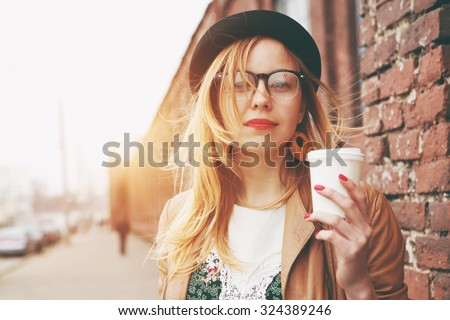 Stylish woman in the street drinking morning coffee - stock photo