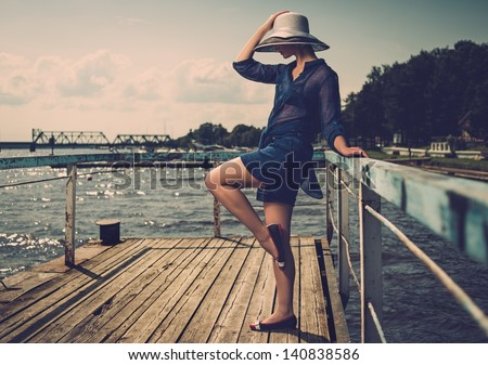 Stylish woman in white hat standing on old wooden pier - stock photo