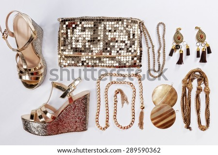 Stylish woman outfit. Golden jewelry, shiny gold purse and sandals, isolated on white background. - stock photo