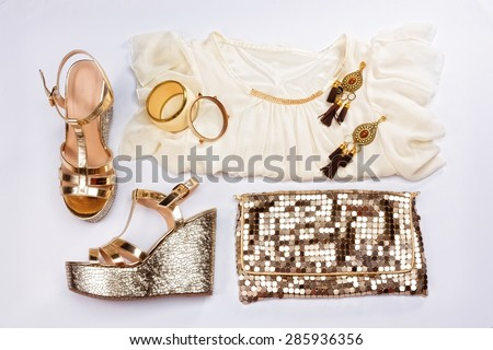 Stylish woman outfit. White summer dress, sandals, golden jewelry and shiny gold purse, isolated on white background. - stock photo