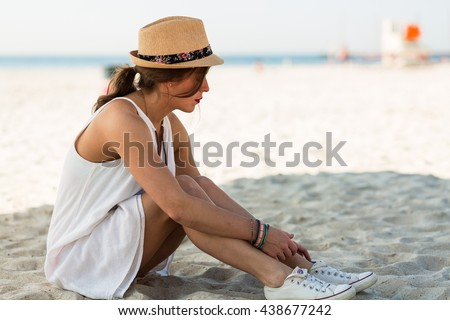 Stylish woman relaxing on a sandy beach at summer