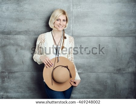 Stylish woman standing front of grey wall, smiling, holding hat.