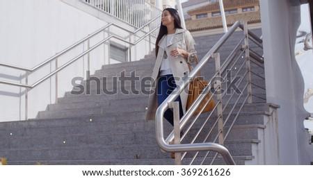 Stylish woman walking down a flight of stairs - stock photo