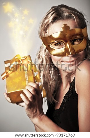 Stylish woman wearing golden mask and holding gift box, celebrating holidays, female receive gold Christmas present, new year eve party - stock photo