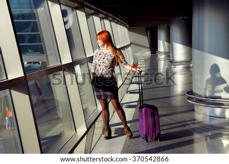 stylish woman with a suitcase standing at the window at the airport. traveler waiting airplane flight