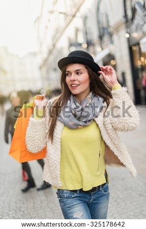 Stylish woman with black hat and woolen jacket doing shopping in the city center. She is smiling, walking in a car-free cobbled street. She is holding yellow and orange shopping bags - stock photo