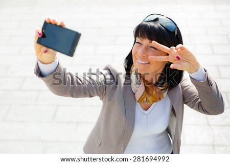 Stylish woman 30 years, smiling pretty woman taking pictures selfie her phone and have fun, dressed in suit, sunny day, city street, soft light series, Positive emotion, facial expression, spring mood - stock photo