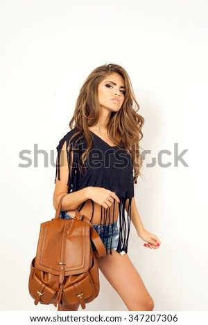 Stylish woman,Young pretty hipster woman in black trendy t-short,amazing outfit white wall.Have perfect long wavy hairstyle,casual clothes,boho chic outfit - stock photo