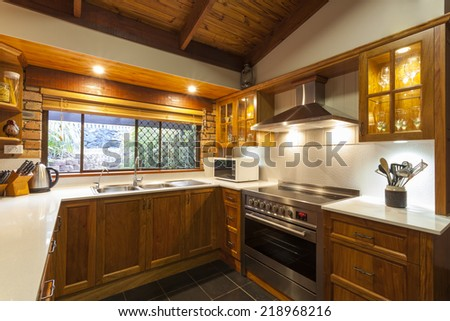 Stylish wooden kitchen interior with white stone top - stock photo